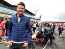 Football player Michael Carrick on the grid next to the car of Max Verstappen