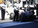 Team members push Fernando Alonso into the garage in the pit lane.